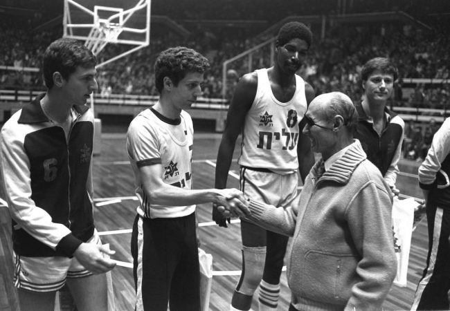 MK MOSHE DAYAN SHAKING HANDS WITH MACABBI TEL AVIV BASKETBALL PLAYER MOTTI AROESTI, AS AULCI PERRY & MIKY BERKOVITZ LOOK ON AT THE YAD ELIYAHI STADIUM. (ON THE MAP)