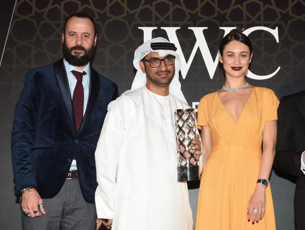 DUBAI, UNITED ARAB EMIRATES - DECEMBER 08: Ali Suliman, Actor (L), Abdullah Hassan Ahmed, Director (C), Olga Kurylenko , Actress and model (R) attends the fifth IWC Filmmaker Award gala dinner at the 13th Dubai International Film Festival (DIFF), during which Swiss luxury watch manufacturer IWC Schaffhausen celebrated its long-standing passion for filmmaking at One And Only Royal Mirage on December 8, 2016 in Dubai, United Arab Emirates. (Photo by Stuart C. Wilson/Getty Images)