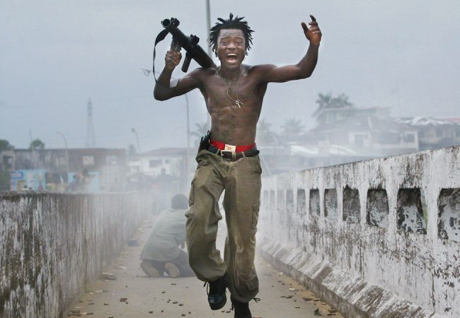 Liberia soldier Joseph Duo exults after firing a rocket at rebel forces in Monrovia, Liberia in 2003. The photo led to an unlikely and enduring friendship between the subject and the photographer, Getty Images photojournalist Chris Hondros. Film still from HONDROS. Photo by Chris Hondros.