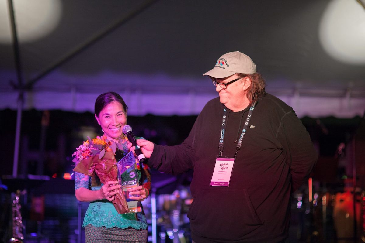 Director Sotho Kulikar of The Last Reel accepts the Founders' Prize for Best Film with Michael Moore at Traverse City Film Festival