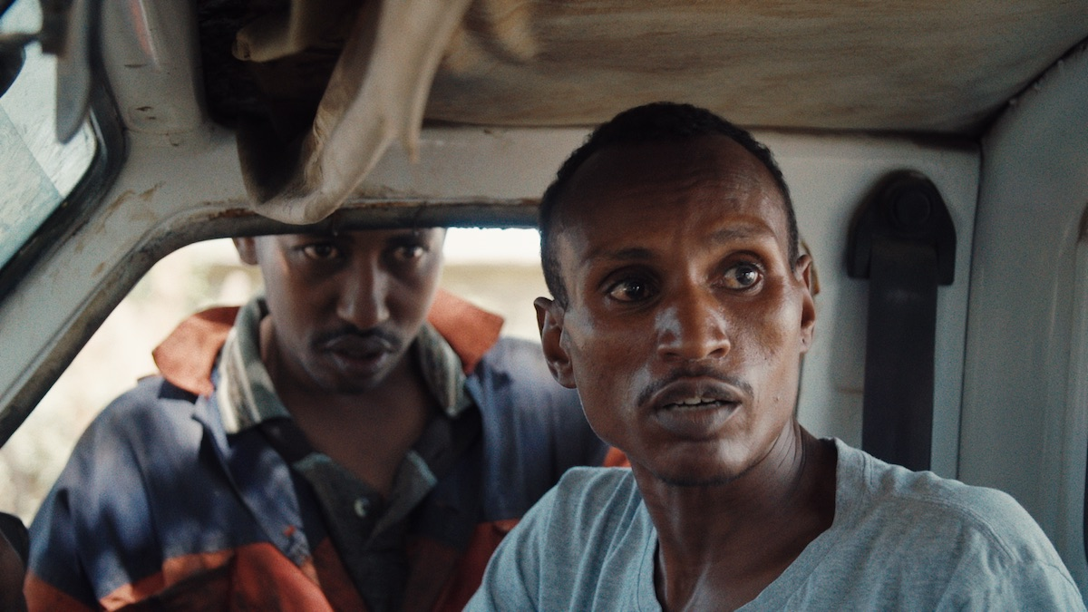 "Ivory dealer ""X"" (outside car window) and poacher Lukas wait for the wildlife rangers to pass. From When Lambs Become Lions, directed by Jon Kasbe. Courtesy of Kasbe Films / The Documentary Group."