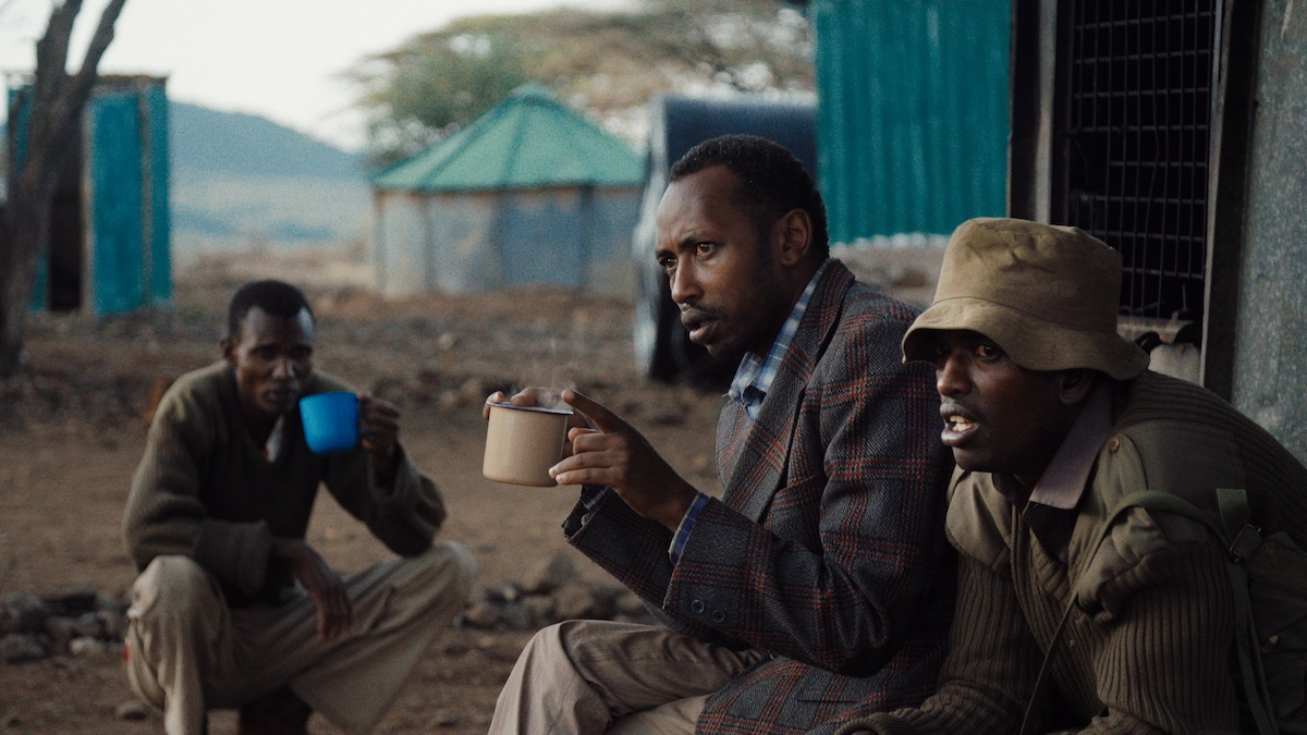 "Ivory dealer ""X"" (left in foreground) visits the wildlife ranger unit of his cousin Asan (at right). From When Lambs Become Lions, directed by Jon Kasbe. Courtesy of Kasbe Films / The Documentary Group."