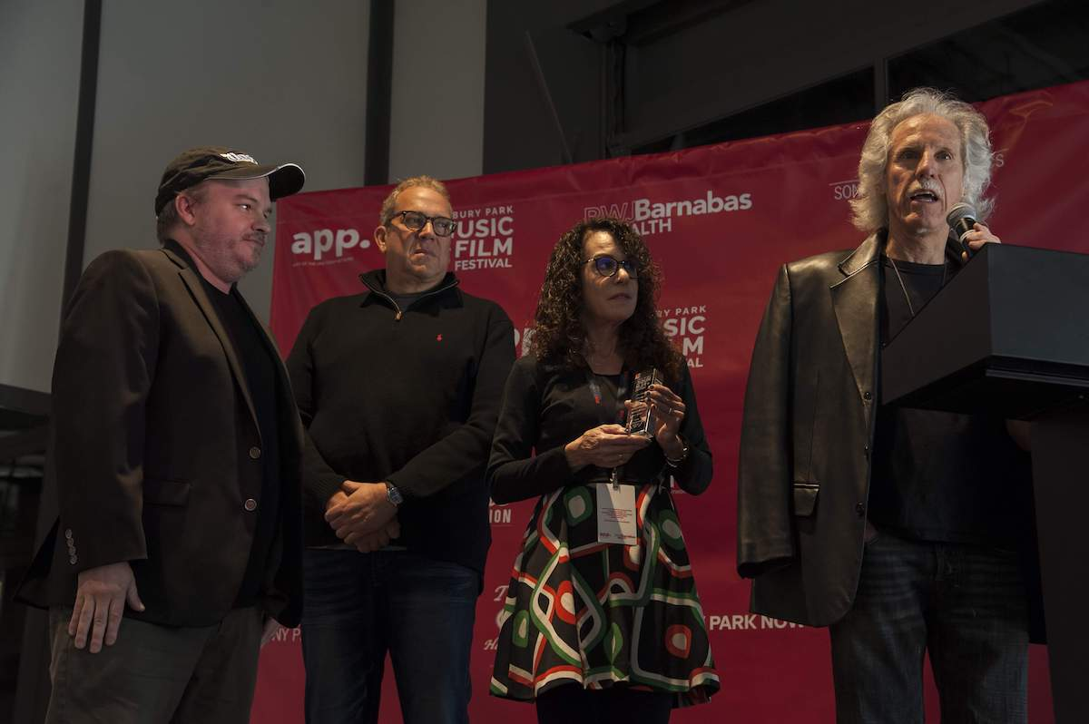 "Justin Kreutzmann, director; Jeff Jampol of Jampol Artist Management; Shelli Sonstein of Q104.3 FM; and John Densmore of The Doors receiving the APMFF Best Film Feature Award for Kreutzmann's ""Break On Thru: A Celebration of Ray Manzarek and The Doors."" - (APMFF)"