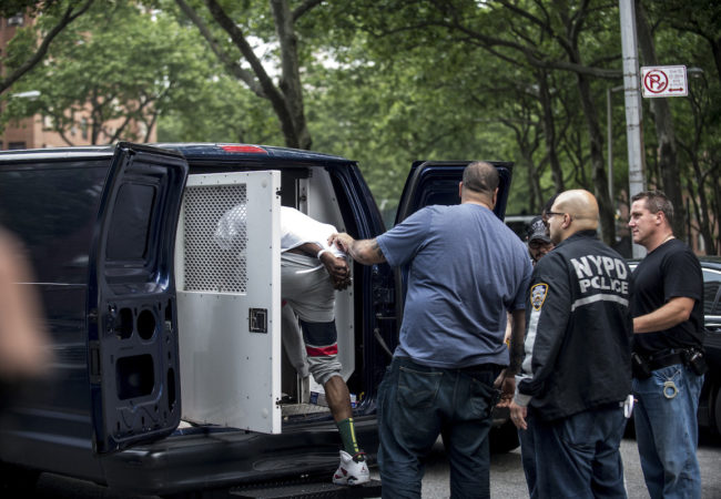 One of the dozens of suspected gang members corralled in simultaneous early-morning raids is led into a police van in the Harlem neighborhood of New York, June 4, 2014. The indictment cites 103 people, roughly 30 of whom were already in jail, with two killings, 15 shootings, and a host of other crimes. (Robert Stolarik/The New York Times) via The Intercept
