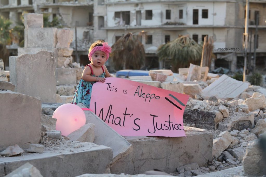 "FOR SAMA. Sama pictured in September 2016, in the bombarded east of the city with a placard in response to US presidential candidate Gary Johnson's infamous gaffe ""What's Aleppo"" – Courtesy of Channel 4, Copyright Waad al-Kateab."