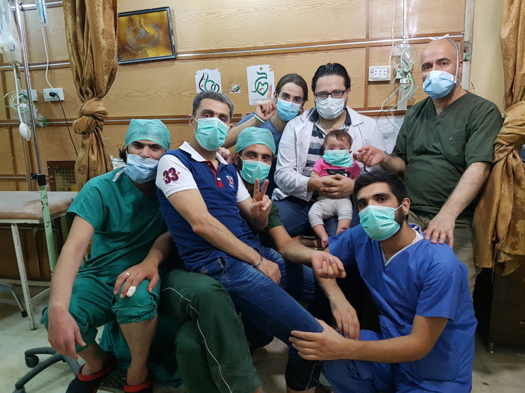 FOR SAMA. Hamza, Sama and the staff of al-Quds hospital, which Hamza set up in 2012 in east Aleppo. Courtesy of Channel 4, Copyright Waad al-Kateab.