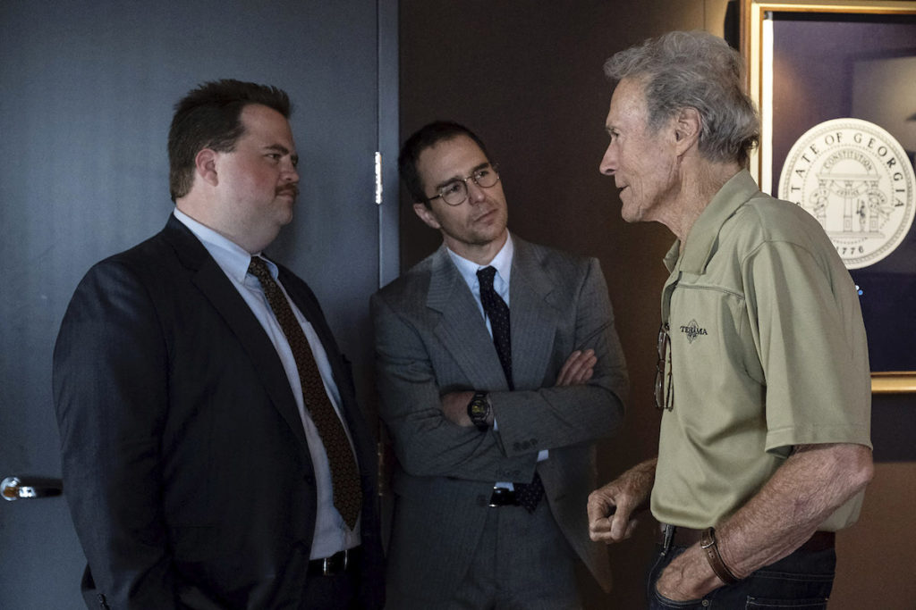 """(L-R) PAUL WALTER HAUSER, SAM ROCKWELL and CLINT EASTWOOD on the set of Warner Bros. Pictures' """"RICHARD JEWELL,"""" a Warner Bros. Pictures release. Photo by Claire Folger"""