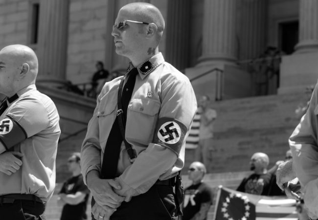 "Members of the National Socialist Movement march down the streets of Columbia, South Carolina to the steps of the State Capital building. April 21, 2007., Columbia, S.C. They rally to protest the ""3rd world invasion"" of illegal immigrants and the thousands of Mexicans shutting down major cities demonstrating against border reform and their refusal to assimilate into American culture. During the rally, the NSM announced their third party candidate for the upcoming US Presidential election John Taylor Bowles. Bowles is a veteran of the United States Air Force and has been in the NSM for over 30 years. The National Socialist Movement had upwards of 100 supporting members and were met by a vocal crowd of counter protesters. A large police and federal presence kept the event free from incident. (HEALING FROM HATE: BATTLE FOR THE SOUL OF A NATION directed by Peter Hutchison)"
