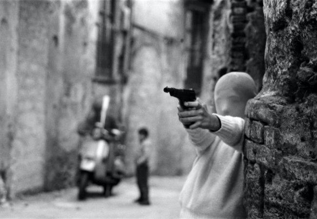 """Film subject Letizia Battaglia's photo Palermo, 1982. Vicino alla Chiesa di Santa Chiara. Il gioco del killer. (""""Palermo, 1982. Near the Church of Santa Chiara. The game of the killer."""") in Shooting the Mafia, directed by Kim Longinotto . Courtesy of Cohen Media Group."""