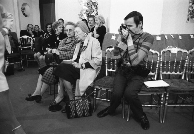 Bill Cunningham, covered in coiled wires, straps and other camera equipment, seated in the fashion show which had no runway so I took a picture of him with the audience. One of the ladies is taking notes. Paris, France, 1971. ©Harold Chapman / Topfoto / The Image Works. Bill Cunningham Paris 1972 - THE TIMES OF BILL CUNNINGHAM - Courtesy of Greenwich Entertainment
