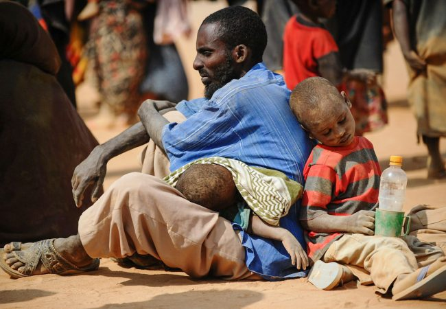 """A Somali man who fled violence and drought in Somalia with his family sits on the ground outside a food distribution point in the Dadaab refugee camp in northeastern Kenya on July 5, 2011. Dadaab, a complex of three settlements, is the world's largest refugee camp. Built to house 90,000 people and home to more than four times that number, it was already well over its maximum capacity before an influx of 30,000 refugees in June. Upon arrival, the refugees find themselves tackling a chaotic system that sees new arrivals go days, even weeks, without food aid. """"It still takes too much time for refugees to get proper assistance,"""" Antoine Froidevaux, Medecins Sans Frontieres's (Doctors Without Borders) field coordinator in Dadaab told AFP. """"The answer in terms of humanitarian aid is not satisfactory at all at the moment."""" AFP PHOTO/Roberto SCHMIDT (Photo by Roberto SCHMIDT / AFP) (Photo credit: ROBERTO SCHMIDT/AFP via Getty Images)"""